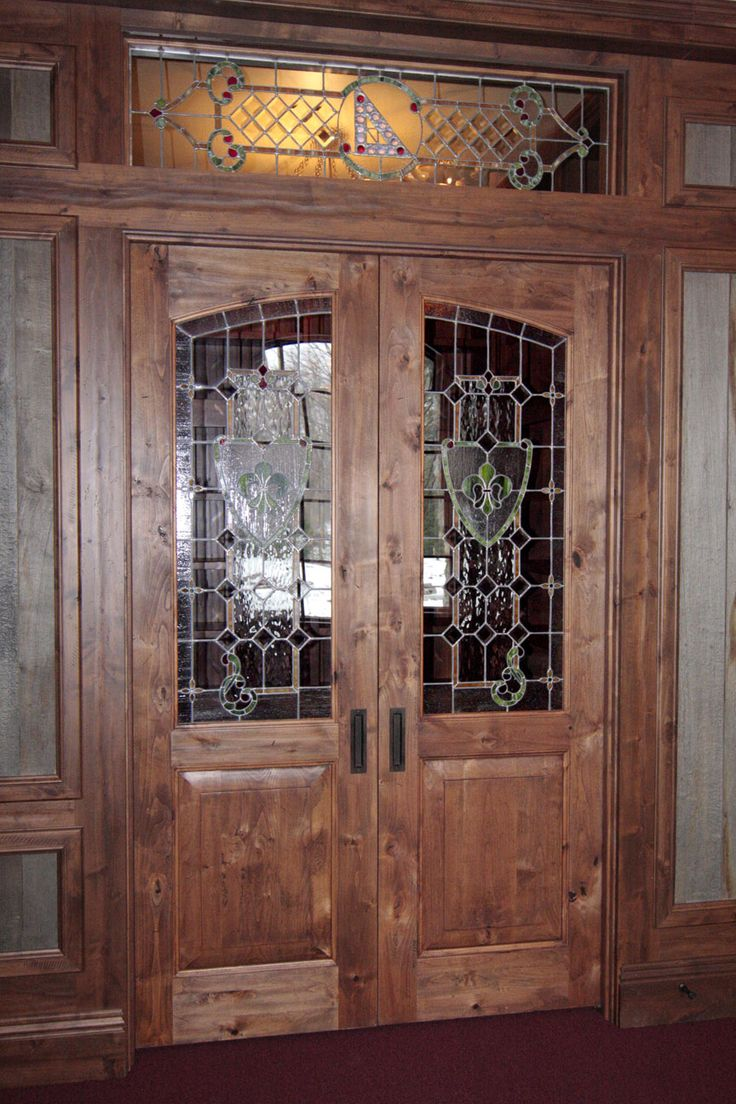 Knotty Alder interior door with stained glass inserts and stained glass transom above. Home built by Martin Bros. Contracting, Inc.