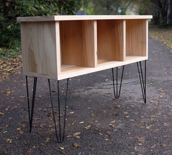 For sale is a custom, handmade vinyl record shelf. The shelf measures 42 wide x 31 tall x 14 deep and will hold approximately 225 records (about 75 per opening). It is made from 1 thick wood and sits on top of custom hairpin legs. The top is 14 deep and designed to hold most record players. This shelf can be ordered in Poplar, White Oak, or Walnut. If you would like another type of wood, please contact me for a quote.  There are some add on options available for this unit. You can have a…