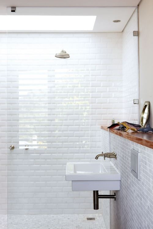 Wall-mounted sink, mosaic tile on floor and wainscot (half wall), beveled subway full height, walk-in shower with rain showerhead, white with wood.