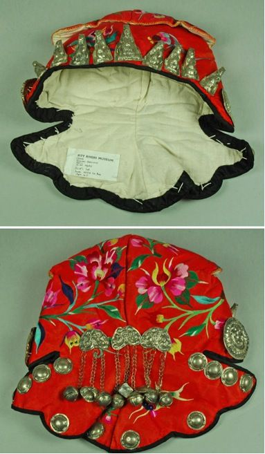 Hand-made child's embroidered and decorated silk hat, representing a tiger. Hmong (Miao) people, Guizhou Province, China, 1980s. A tiger hat scares away evil spirits or fools them into thinking that the child is a fearsome animal.
