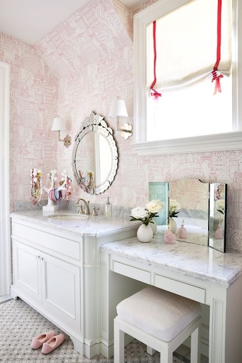 Chic girl's bathroom features venetian mirror on white and pink wallpaper flanked by polished nickel clover sconces over white washstand accented with white carrera marble countertop topped with white jewelry tree over black and white geometric tile floor.