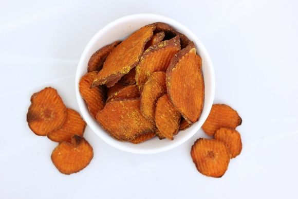 Curried Sweet Potato Chips – Gluten-Free + Vegan 1 large or 2 small organic sweet potatoes, peel on, sliced into 1/8-inch thin rounds 2 tablespoons coconut oil, melted 2-3 teaspoons yellow curry powder 1/4 teaspoon salt Preheat oven to 400ºF. For easier cleanup, line your baking sheet(s) with foil or parchment paper.
