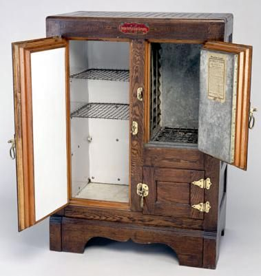 A zinc-lined oak ice box for home use, about 1880. The block of ice fitted into the compartment at left. Cold sir circulated downward to keep food cool. The small door below the ice chamber was the meat compartment, always the coldest part of the box. As the ice melted, water accumulated in a drip tray that had to be emptied, often by the ice man when he loaded a fresh block of ice each day. Better models featured a spigot through which the drip tray could be emptied into a bucket.