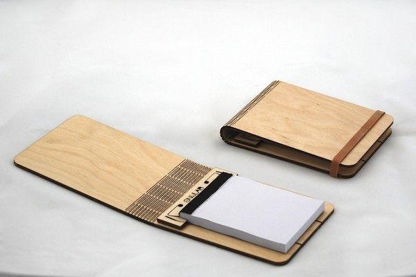 Un taccuino di legno flessibile: la cover rigida può essere interamente ripiegata per impugnare meglio il taccuino aperto. Un piccolo morsetto all'interno, fatto dello stesso materiale, sorregge un blocchetto di fogli formato A7.