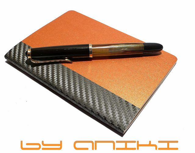"""Aniki Carbon KIM Notebook """"Aniki is called this luxury notebook as a KIM for the reason of our respect and love to 50's famous movie star KIM NOVAK. KIM is a new soft cover member of ANIKI's A6 format notebook family in French cahier style for daily life use as a pocket notebook. Each notebook spin of Carbon series is forced with a special cloth of carbon leafs. It has been build with a collaboration of high-end papers and strong covers to protect your memories for long time."""""""