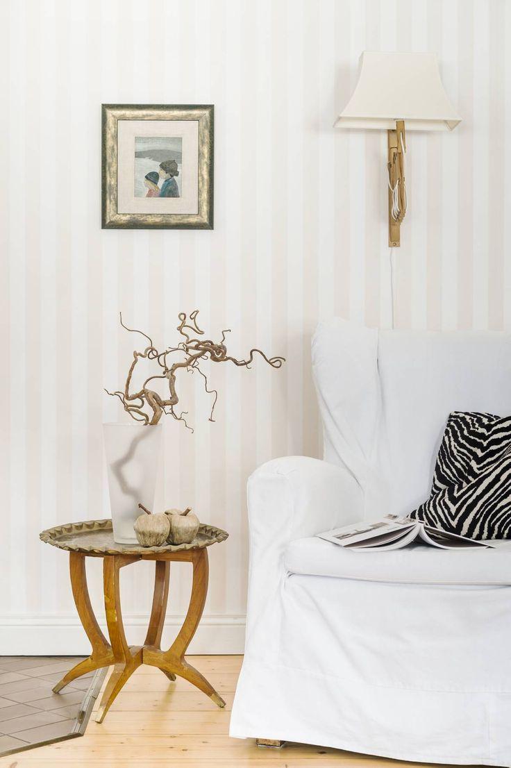 Olohuoneen lukupaikka on suosittu varsinkin talven paukkupakkasilla, kun kaakeliuunissa palaa tuli. Pieni pöytä kuuluu kahden pöydän sarjaan, jonka Raija on ostanut vuosikymmeniä sitten. Vanhaan nojatuoliin on ommeltu pestävä valkoinen huppu. Seinällä on Pentti Koivikon maalaus Sisarukset.