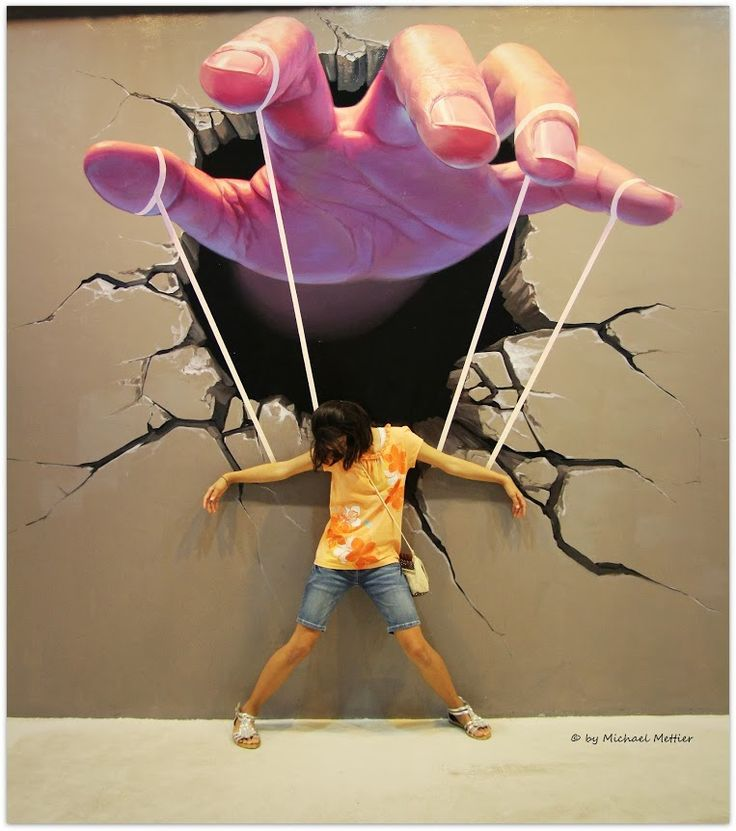 This Urban graffiti art is by Mr Pilgrim. When standing in front of it, it appears as if you are a puppet on a string being manipulated by the large hand above.