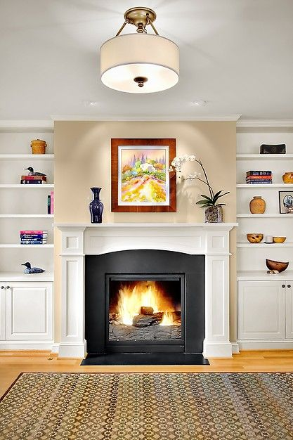 Beautiful and simple mantel. I like the black stone? that they have surrounding the fireplace. Maybe we could do something like that over our existing brick?