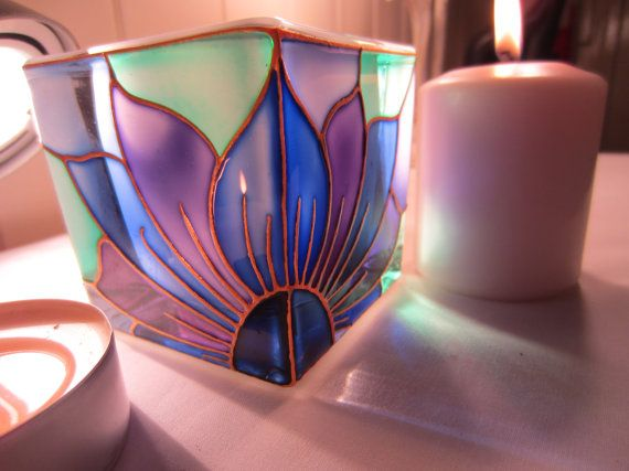 A solid glass candle holder, measuring 9 x 9cm, which I have outlined freehand in shimmering gold coloured relief, and painted using transparent shades of Jade and Purples.  Etsy  $32.62