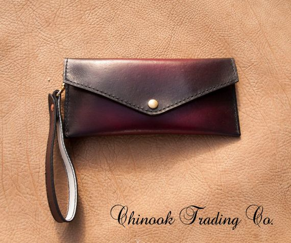 Vegetable tanned womens clutch with wrist strap . Hand cut ,hand dyed , hand stitched .Dyed an ox blood red sunburst to black with black