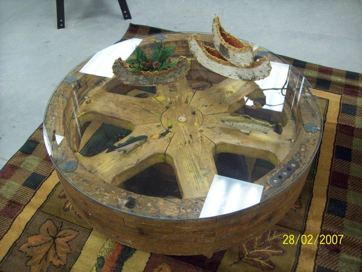 An old mill wheel topped with a piece of glass made a rustic coffee table. I added a couple of fish under the glass to give character.
