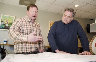 Burnt Hickory Brewery founder Scott Hedeen, right, looks over blueprints that call for the expansion of his facility in Kennesaw with Michae...