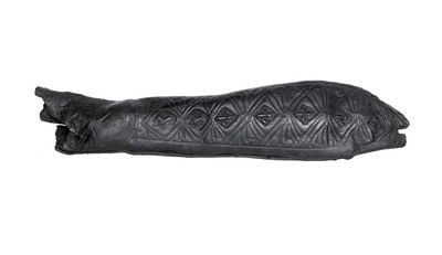 Sheath Incomplete leather knife sheath with impressed and stamped decoration. The top of the sheath is missing. The decoration is in two sections to reflect the handle and blade areas. The blade section swells outwards slightly just above the tip. The front two panels consist of impressed curving and linear motifs and lozenge-shaped frames that contain a mix of small fleur-de-lys and lions rampant stamped motifs.  Production Date: Medieval; 13th-14th century