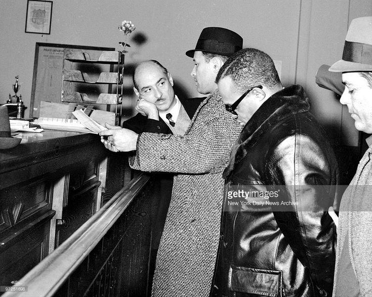 Assistant District Attorney David Blatt (left) and detectives stand by Leroy 'Nicky' Barnes is booked at Bronx police station.