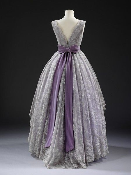 Back view of a 1957 Evening dress by Jacques Fath.  Jacques Fath opened his Parisian couture house in 1937. He quickly became known both for his softly sculpted garments and a talent for self promotion. This dress is likely to have been designed by Fath's wife and muse Geneviève, who upon Fath's death in 1954, oversaw the house until it closed in 1957.