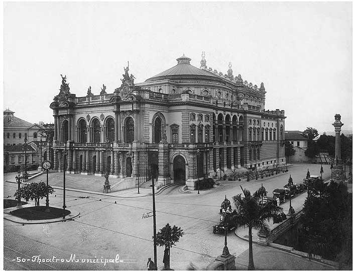 1920 Vista do Teatro Municipal e da praça Ramos de Azevedo, provavelmente a partir do edifício da Light. Com as obras iniciadas em junho/1903, foi inaugurado em 12/setembro/1911 com apresentação da ópera Hamlet, diante de  seus 1.816 lugares lotados e grande congestionamento de automóveis nos arredores.