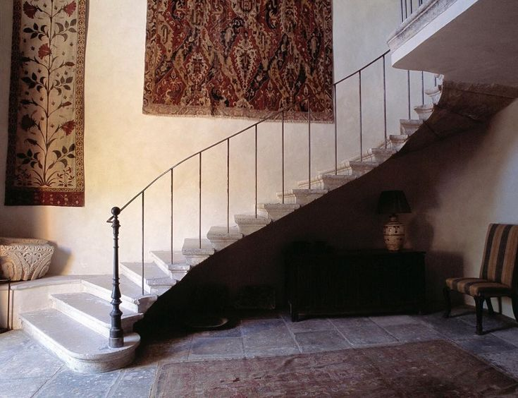 La Gonette, Provence. Above this gracefully curving cantilevered stone staircase hangs a Mughal printed panel and an 18th Century Dragon carpet. Below the stairs is a linen-fold chest bearing a Chinese lamp.   #lagonette #house #provence #france #design #interior #robertkime #stone #staircase