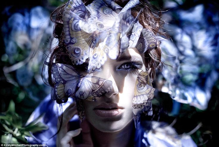 Danaus: A close-up of a model before a sunlit backdrop, peering through a veil of paper butterflies