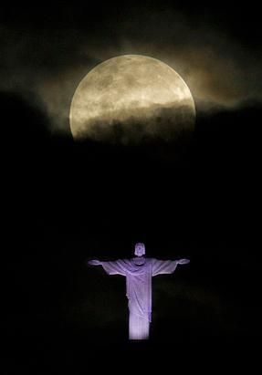 """A """"supermoon"""" is seen above the Christ the Redeemer statue in Rio de Janeiro, Sunday, May 6, 2012. A supermoon is the coincidence of a full moon (or a new moon) with the closest approach the moon makes to the Earth. (Victor R. Caivano/AP Photo)"""