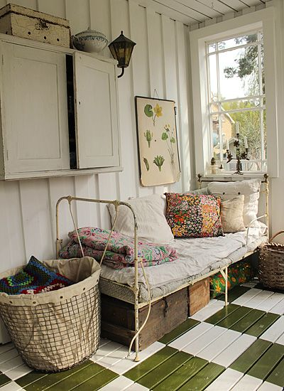"""Darling """"sunroom"""" with vintage daybed (bed) colorful pillows, baskets, and a painted floor."""