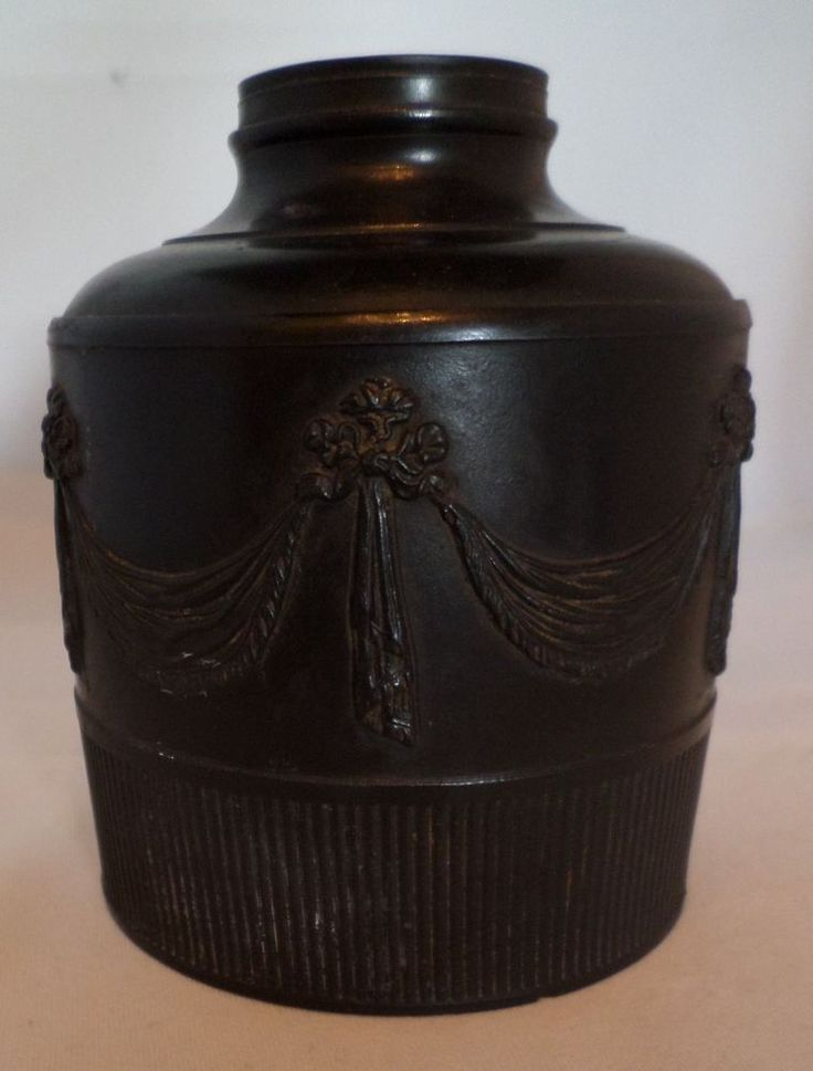 Late 18th century black basalt tea canister  | eBaySprigged with beautiful swags on a polished ground over a reeded bottom section.  It us unmarked. Circa 1790?  Size; 10cms high, base 8cms  Condition; the actual canister is good except for a tiny chip to the base, BUT some of the swags are missing (sheared straight off with no sign on the body!) and one tassel lacks its final frill.  £37