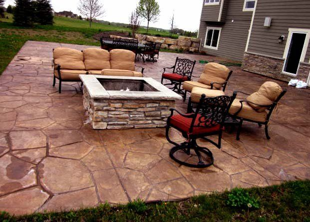 Colored And Stamped Concrete Patio With Stone Fire Pit