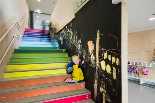 Šmartno Kindergarten designed by Jure Kotnik | The stairs leading up to this slide not only enticing much exercise, but with the colours, numbers and blackboard wall also acting as a teacher and inviting interaction. (Note the adult and child-sized railings also).