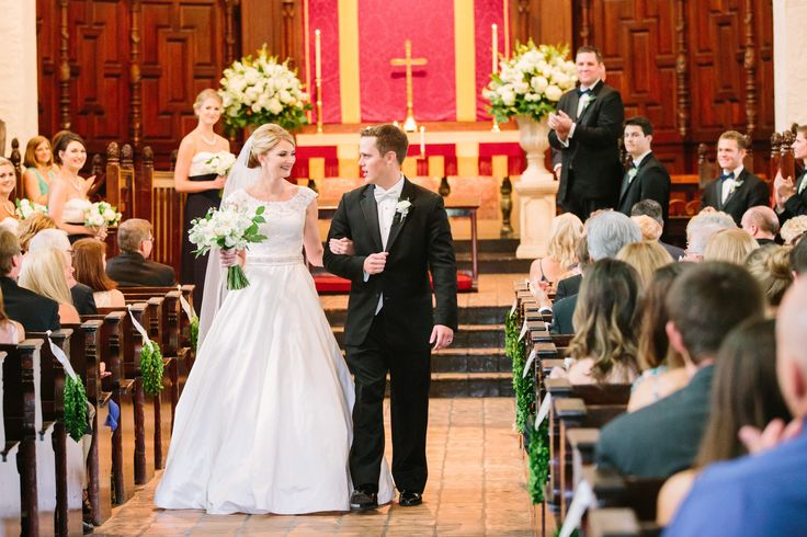"after saying ""i do"" the bride and groom recess down the chapel aisle lined with pew markers of boxwood wreaths and classic altar urns filled with fresh white and ivory flowers and spring greenery."