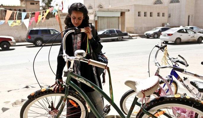 """""""Wadjda"""" by Haïfaa Al Mansour De tienjarige Wadjda wil heel graag een fiets kopen om tegen haar vriendje Abdul te kunnen racen. Er zijn wat hobbels op de weg: ze heeft geen geld en Saoedische meisjes horen niet te fietsen. Het moderne sprookje Wadja is de eerste speelfilm die volledig in Saoedi-Arabië werd gedraaid. Een land waar bioscopen verboden zijn, vrouwen ondergeschikt zijn aan mannen, geen auto mogen rijden en alleen in een alles bedekkende zwarte kleding over de straat mogen."""
