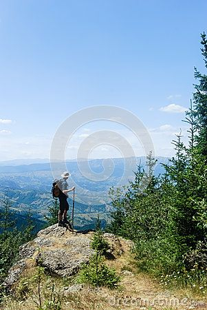 One young man looking at the back country as he walks in the mountains. In front of him there is a valley and beyond an other mountain.