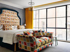 Яркая спальня в стиле неоклассика. Оранжевый, серый, кровать, диван, шторы, панорамное остекление, высокое мягкое изголовье, люстра-фонарь