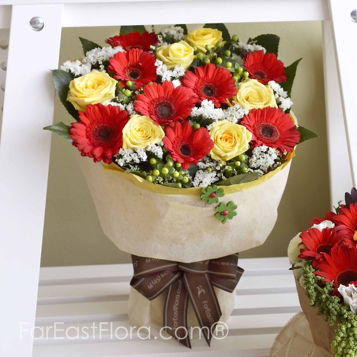 PT26 - Colors Of The Sun  You embrace the colors of the sun when you have this bouquet in your arms. Sunshine yellow roses and sunset red gerberas blossoms among white forget-me-nots, like the sky at dusk, sporadically flecked with distant clouds.