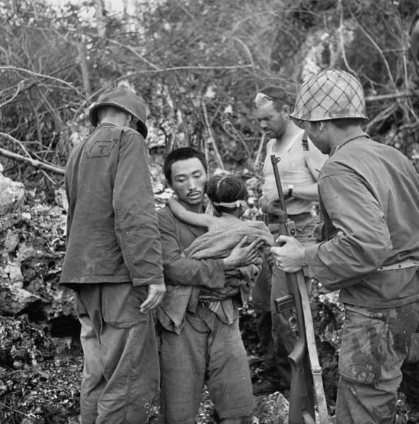 American GIs helping starving, frightened father & child who are surrendering to them after the battle for control of Saipan. July 1944.