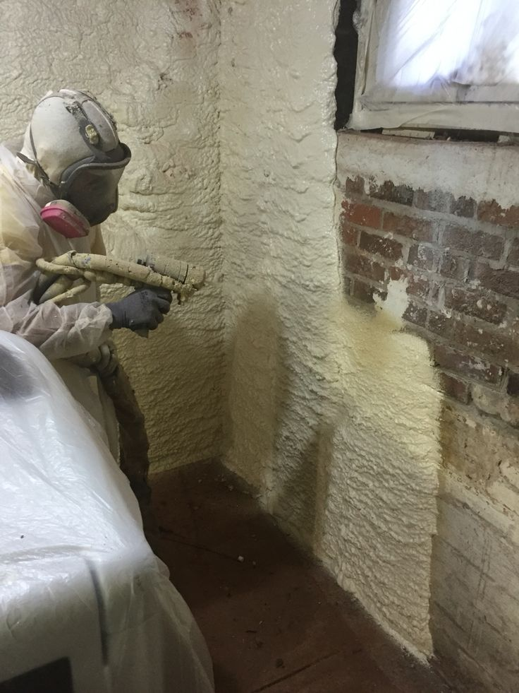 Spraying closed cell foam insulation on the basement walls to make older home in Raleigh more efficient. Installed by mpifoaminsulation.com