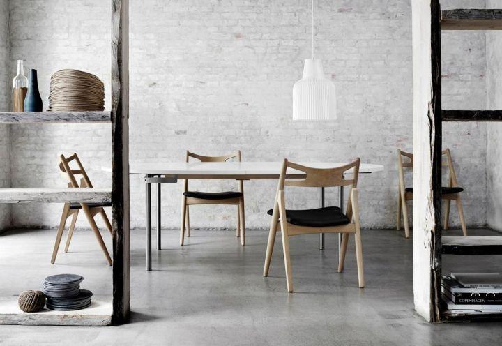 Uno dei mini ambienti racchiusi all'interno del locale Höst di Copenhagen, migliore ristorante nell'ambito dei Restaurant & Bar Design Awards 2013. Pavimento in cemento colato, pareti con muratura a vista e le linee sinuose delle CH24 e CH29 chair di Hans Wegner