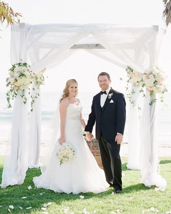 A Birch Gazebo With Sheer White Draping Pulled Back Like