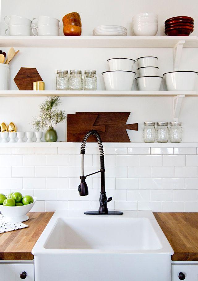 Butcher block counters, apron sink, subway tiles, open shelves.