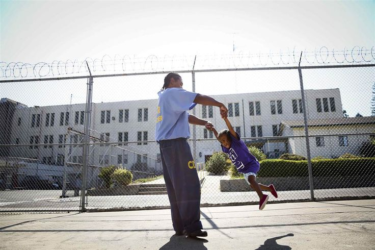"Pharaoh Haywood plays with his daughter Isis, 2, during a ""Get On the Bus"" visiting day to Folsom State Prison on July 26. The California De..."
