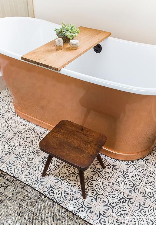 A freestanding copper tub sits on white and gray quatrefoil floor tiles beside a small wooden stool.