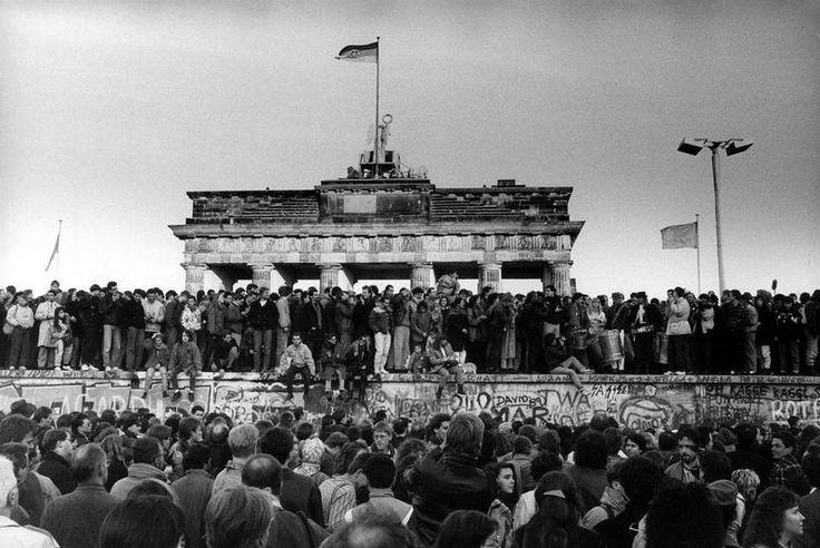 Una impresionante imagen de la multitud subida al Muro frente a la Puerta de Brandeburgo, en la que ondea la bandera de la RDA |Daniel Biskup