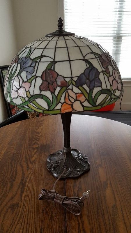 """Vintage oak round entry table on small casters, with Tiffany-style table lamp. Table has 42""""diam x 28.5""""H, dark stain. Lamp has metal base and stained-glass looking plastic shade, 23""""T (shade 16""""diam). Both pcs very good condition"""