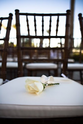 wedding in memory of ideas - a flower laid on a empty chair to signify the presences of lost loved ones