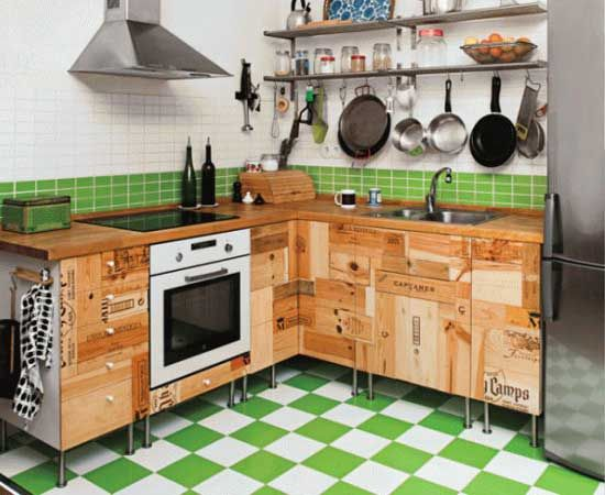 Cuts of wine and beer crates are arranged in vertical and horizontal position to cover the whole front side of L shape kitchen cabinet. On the top part of counter, varnished wood looks smooth installed by electric stove on the left side and faucet on the other side.