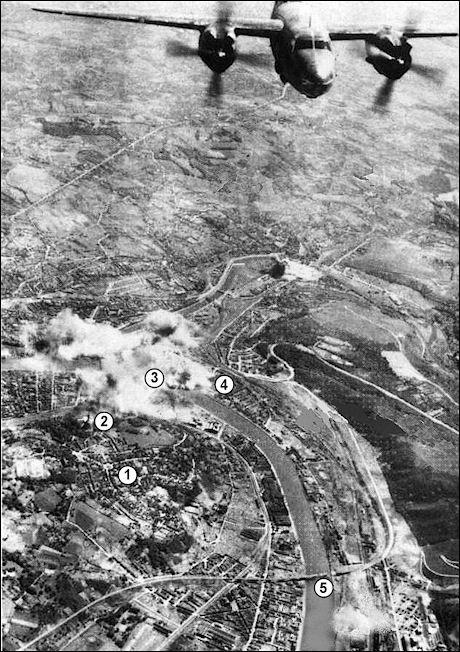 Liège, mai 1944. Le quartier de Fragnée sous les bombes américaines, lors du pilonnage du Val-Benoît par des B-26 Marauder de l'USAF.  On aperçoit le parc privé de Cointe (1), le mémorial interallié (2), le viaduc de Renory (5) ; les fumées des bombardements masquent le pont ferroviaire du Val-Benoît (3) et la gare de triage de Kinkempois (4).