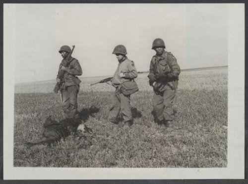 Drie Amerikaanse soldaten van de 10e Infanteriedivisie bij een lijk van een Duitse SS-er
