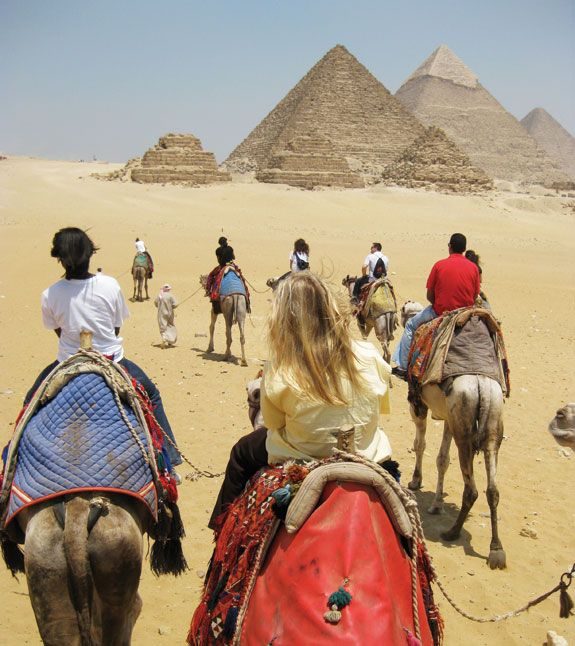 Riding a camel in Egypt towards the Great Pyramids of Giza. Some of those camels have a nasty attitude! I rode one of those.
