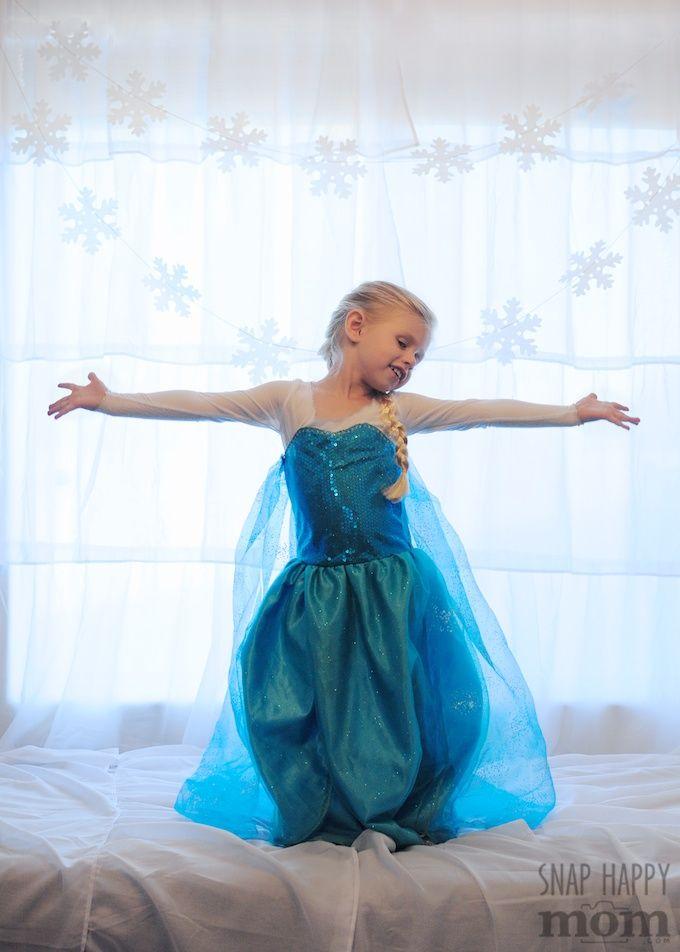 I like the girl's pose, so cute!!!!  DIY Frozen Backdrop for Fancy Elsa Photos - SnapHappyMom.com