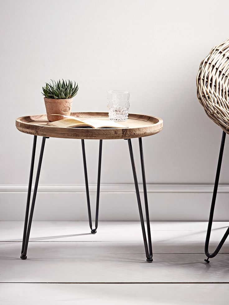 Beautifully carved from firwood with a natural finish that boasts exposed wood grain details, our simple round table has three hairpin black iron legs. This simple, rustic table is perfect for beside your favourite arm chair and also looks great beside your bed.