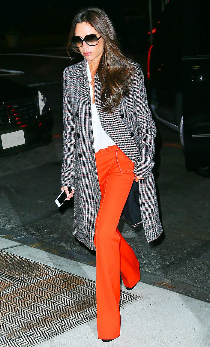 Victoria Beckham wears a white top, orange trousers, and a plaid coat