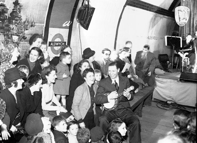 Entertainer George Formby entertains people sheltering in the London underground from German bombing raids, 1940.
